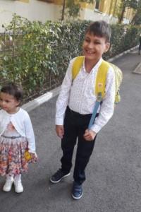 băiat și fetiță pe strada. Băiatul râde, este mai mare, poartă ghiozdan în spate