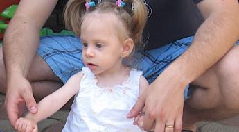 Tată ținănd o fetiță de mânuțe