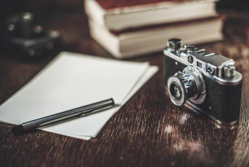 foi de hârtie, stilou, aparat foto vechi si cărți pe o masă