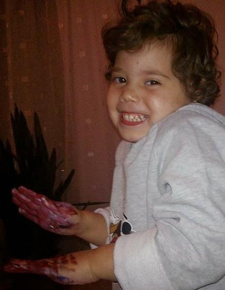 Fetiță veselă cu mâinile murdare de vopsea