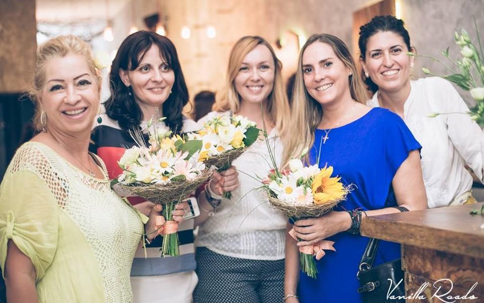 Femei zâmbind și avănd buchete de flori în mâna