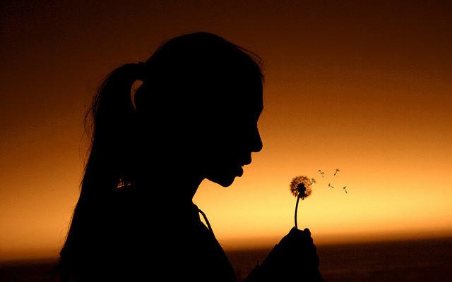 Tănăra femeie, la apusul soarelui, suflă într-o păpădie punându-și o dorință