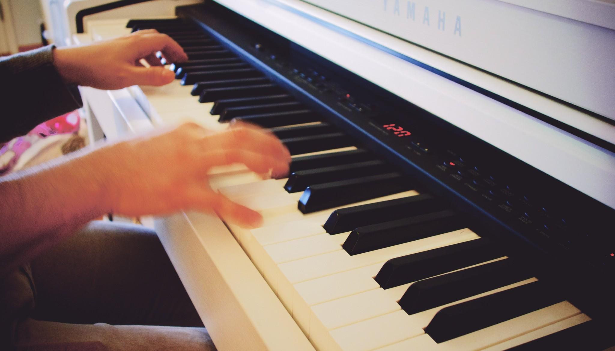 Băiat cântând la pian, se văd numai mâinile pe clape