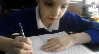 Băiat la lecții, aplecat deasupra caietului