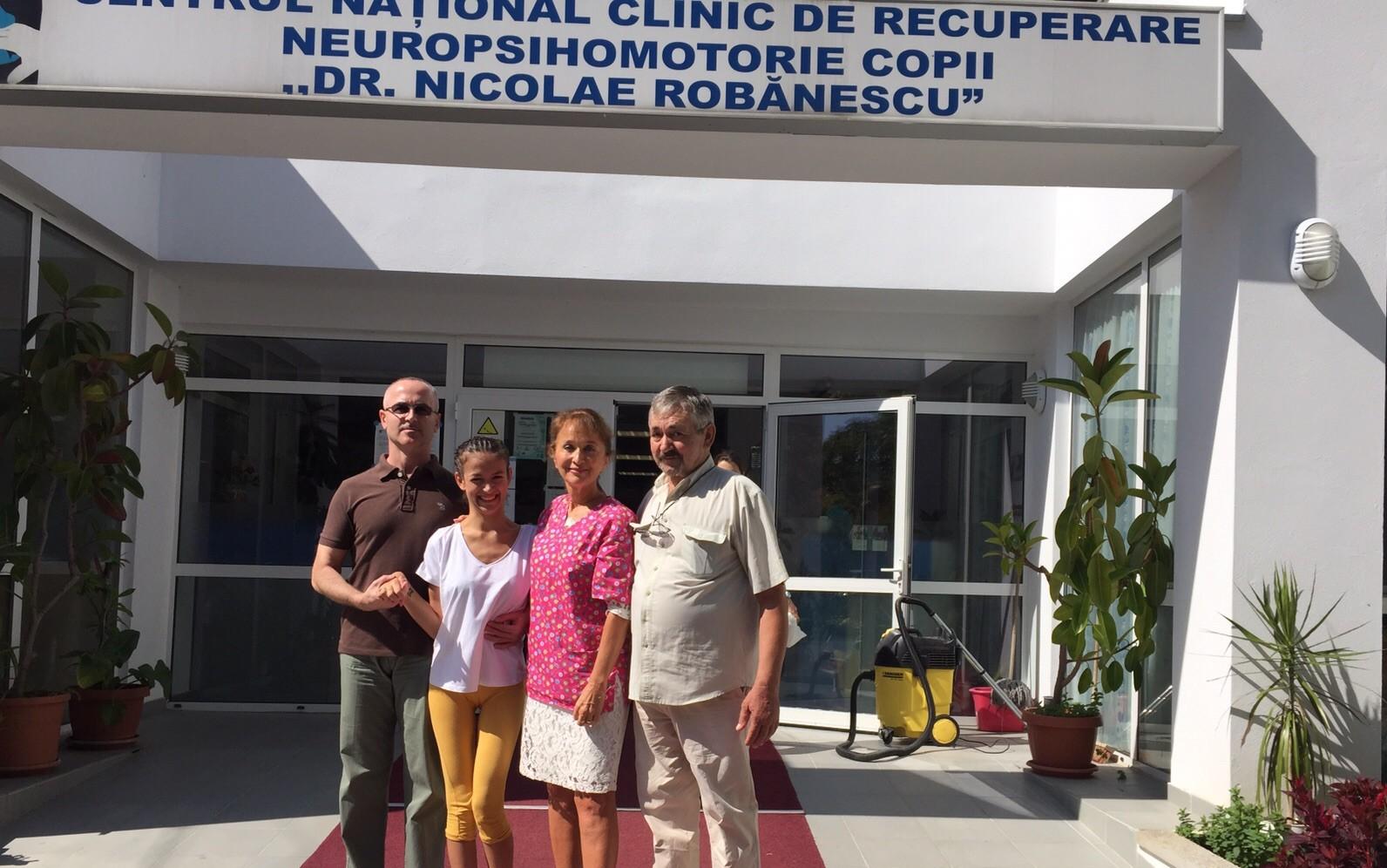 Luana Tudor, împreuna cu echipa sa: bunicul , medicul și kinetoterapeutul, în fața Centrului de recuperare