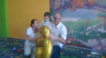 Familie cu baiat mic, zămbind fericită și ținându-se în brațe