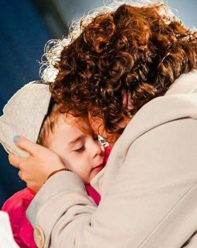 mamă îmbrățișându-și băiatul