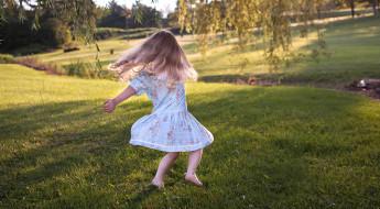 copil sărind în iarbă