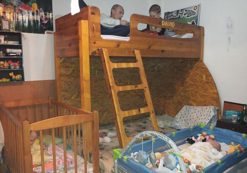 cameră cu patru paturi și 5 membri ai unei familii