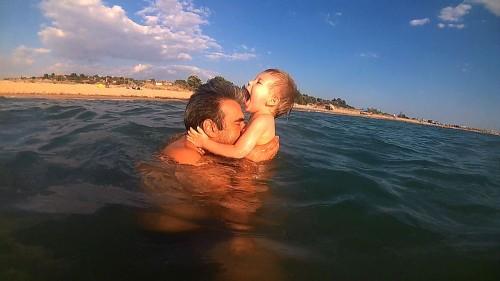 băiat râzând, ținut de tată în brațe, în apă