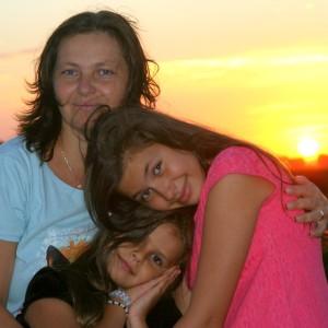 Mama și două fiice, fiica cea mare ține capul pe umărul mamei, fiica cea mică în prim plan, toate trei zâmbesc. În spate se vede apus de soare