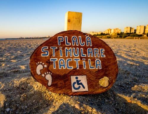 Semn asezat pe plajă pe care este inscripționat: plajă stimulare tactilă si pictograma ce semnifica dizabilitatea