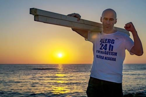 bărbat la malul mării, tine pe umar o stiva de lemne, poartă un tricou pe care scrie Alerg 24 de ore pentru autism marea neagră