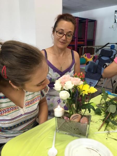 mama si fiica privesc un aranjament floral