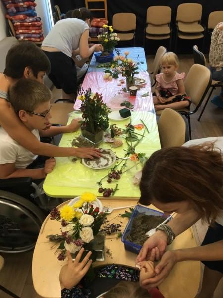 copii cu dizabilități la masă, lucrează aranjamente florale ajutați de adulți