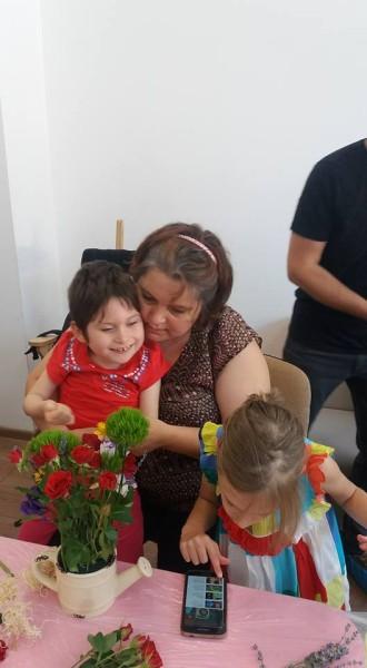 fetită cu paralizie cerebrală, în brațele mamei, atinge o floare