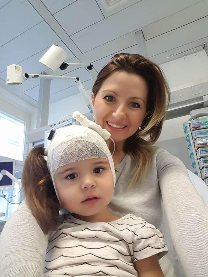 copil în spital, în brațele mamei, are capul bandajat