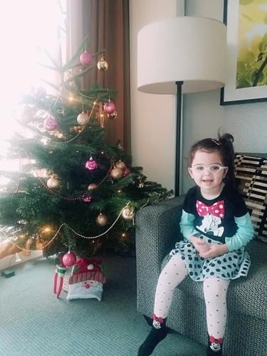 fetiță lângă bradul de crăciun