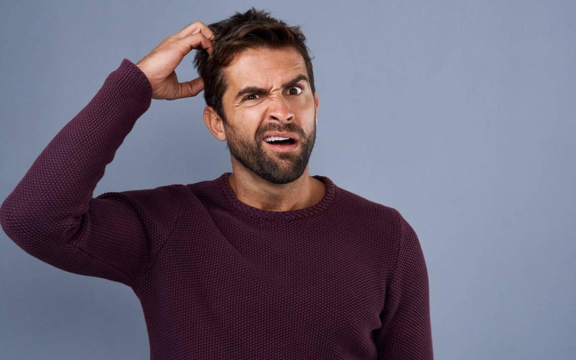 Fotografie de studio, pe fundal gri, a unui bărbat tânar ce se scarpină în cap, expresia sa este de nedumerire, poartă un pulover cu mânecă lungă.