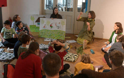 Copii în cerc, pe podea, ascultă o poveste