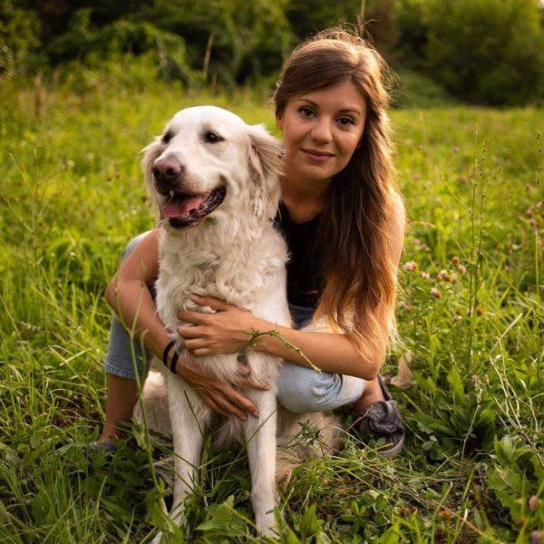 Happy, câine de talie mare, urechi mari, lățoase, păr ondulat pe piept, coadă stufoasă. Alături, terapeutul Carla își ține brațele în jurul câinelui. Carla are părul lung. în fotografie stă pe vine.
