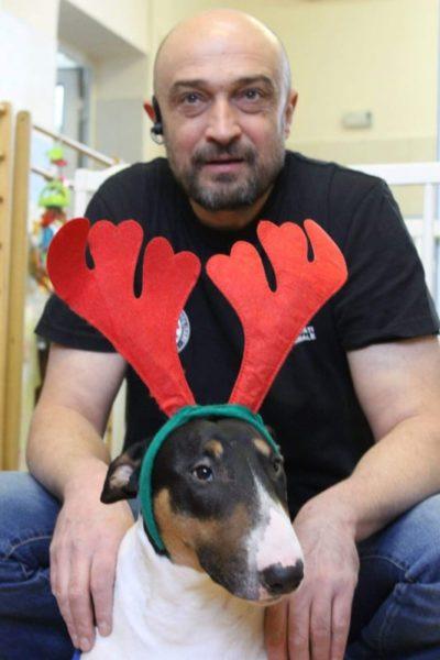 Horia cu cațelușa Molly. Bărbat ținând mâinile pe spatele unui câine de talie medie, păr scurt. Câinele poarta pe cap urechi de jucărie de ren, precum cele de Craciun. Horia are barba scurtă, fără păr pe cap.