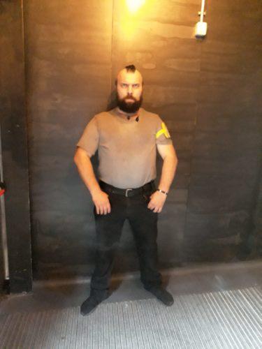 Ilie, bărbat, agent de pază, barbă deasă, lungime medie, păr tuns tip creastă în vârful capului, ras în părți
