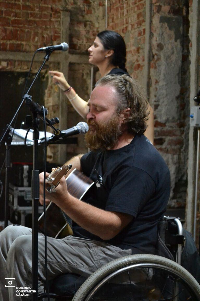 O secnă de concert. În spatele scenei, un perete de cărămidă. Pe secnă, artistul Florin Mândru Dudu, în scaun rulant, cu o chitară în mână. Dudu are barbă și păr creț. Alături de el, interpretul mimico gestual