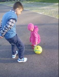 Doi copii jucându-se cu mingea