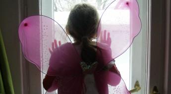Fetiță purtând aripioare de fluturaș privind zapada de afară