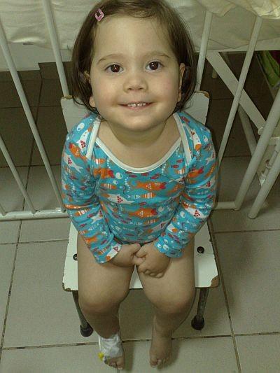 Fetiță de aproximativ doi ani zambind, stând pe scăunel într-un spital