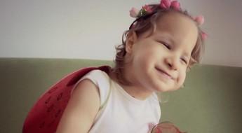 Fetiță imbrăcată în rochiță roșie, purtând aripioare în spate și zâmbind