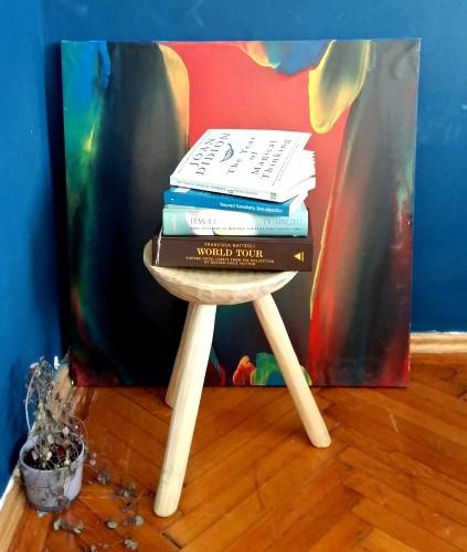 Scaun rustic de lemn pe care sunt așezate cărți
