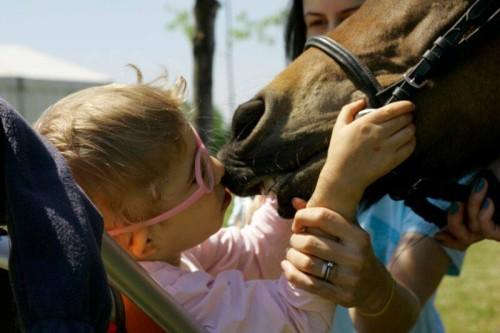 Fetiță sărutând un cal