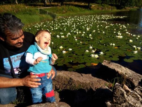 băiat râzând, ținut de tată în brațe
