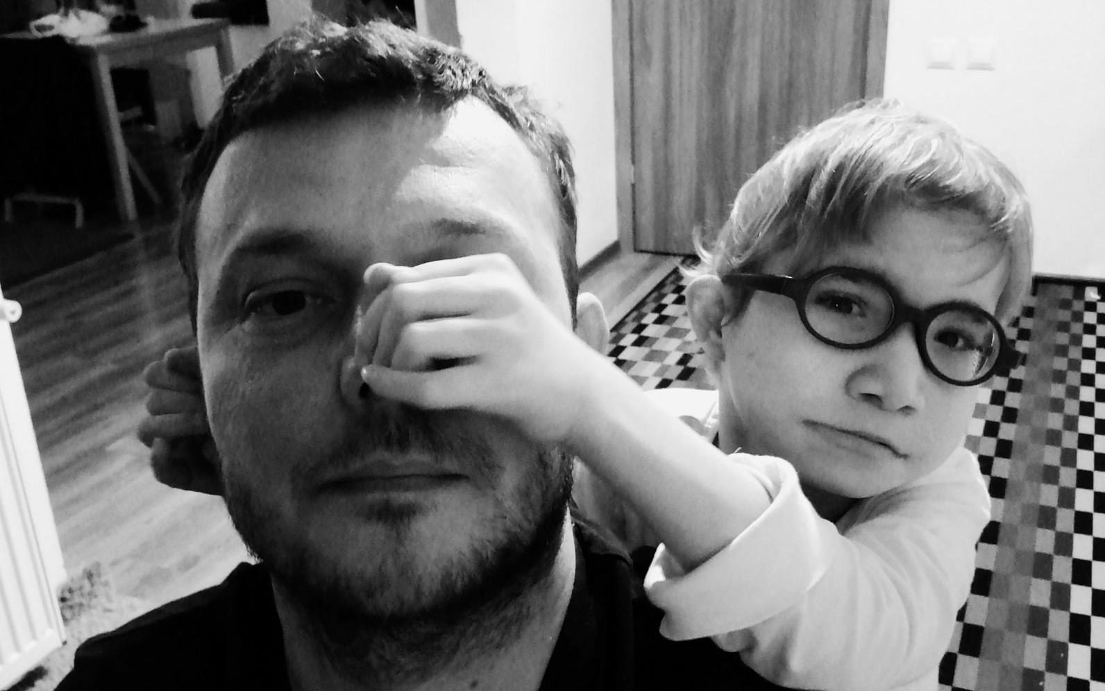 fetiță purtănd ochelari care își trage tatăl de nas. Fața tatalui este acoperită de mănuța fetei. Fetița îl ține cu cealaltă mâna de ureche. Tată este în prim plan. Amăndoi privesc spre cameră