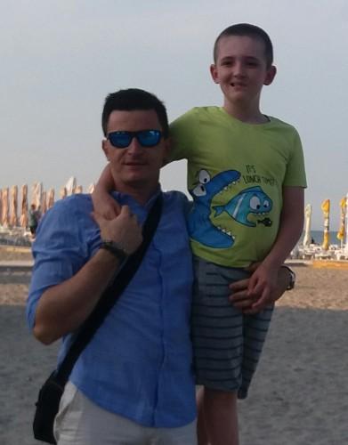 Tată și fiu, se țin de după umeri, pe plajă