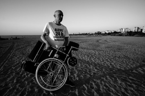bărbat pe plajă, ține în mâini un scaun rulant