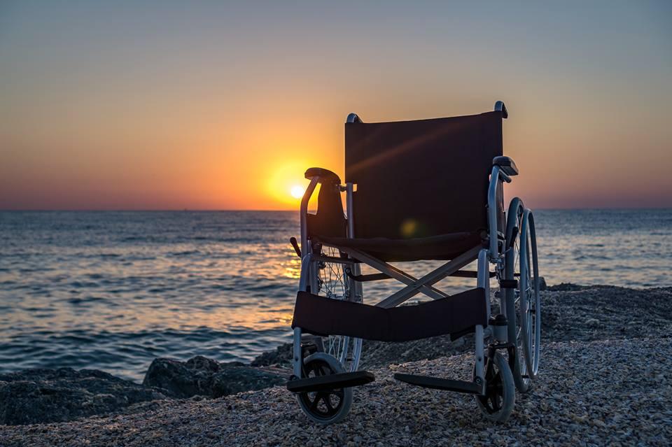 scaun rulant la malul mării, apus de soare