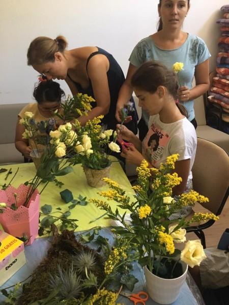 parinți ajută copiii în scaun rulant să poata atinge florile dintr-un vas
