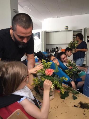 tatăl ajută fiica în scaun rulant să poata atinge florile dintr-un vas