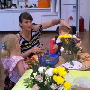 mamă ajutându-si fiica cu dizabilități să privească un aranjament floral