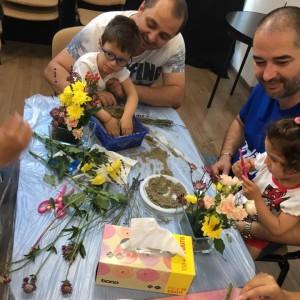 copii, în brațele taților lor, se joacă cu nisipi într-o cutie de pe o masă