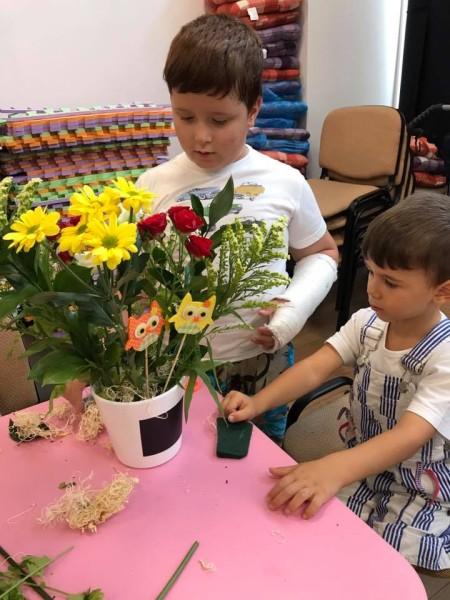 copii privind un vas cu flori