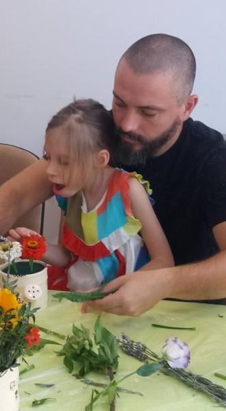 tată și fiică aranjează flori în vas