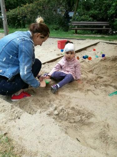 copil la groapa cu nisip, se joacă