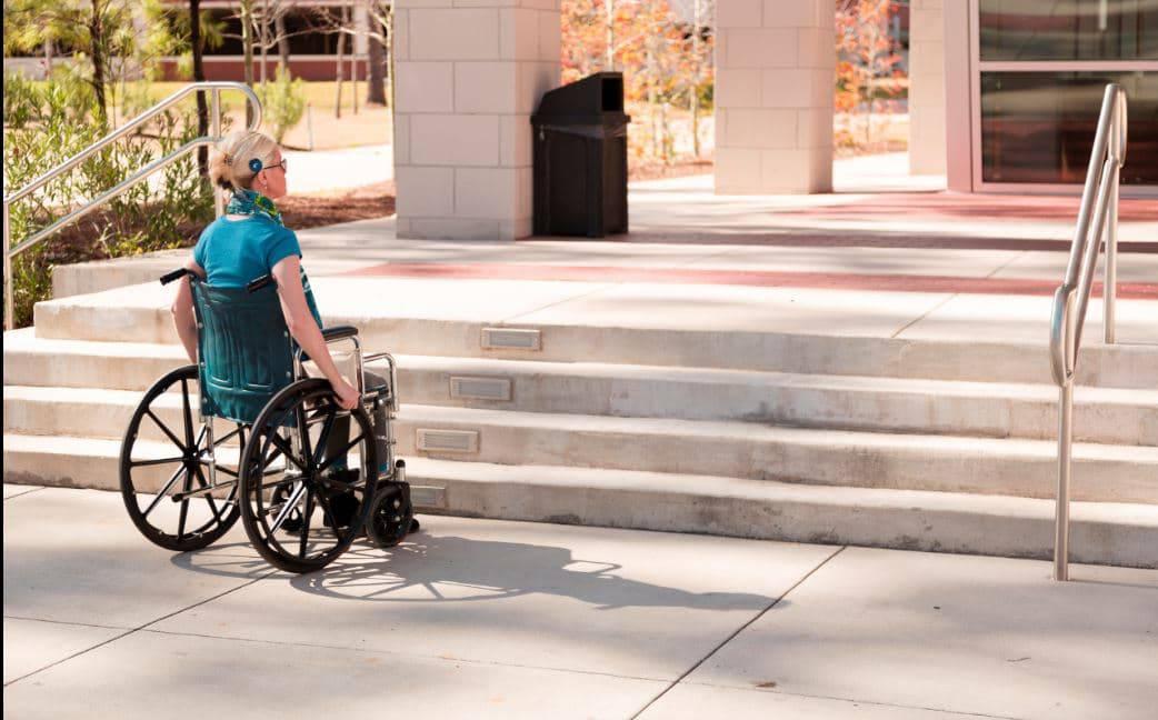 femei în scaun rulant în fața unor scări inaccesibile, lipsă rampă