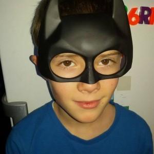 băiat, poarta o mască de supererou, privește zâmbind spre cameră