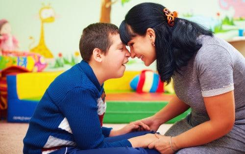 portret emotionant al unei mame împreună cu băiatul său într-o camera de terapie. Se îmbrățișează și zâmbesc