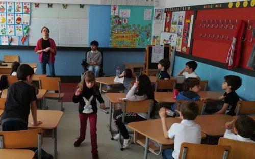 clasă de școală, câțiva copii stau în bănci, o fetiță se plimbă prin clasă, în fața băncilor un elev în scaun rulant
